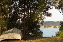 Umgedrehtes Ruderboot auf dem Ufer von einem ruhigen Fluss im moosigen Punkt NSW Lizenzfreie Stockfotos