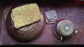 Umgekehrte Metall-Schalen liegen auf einer Burgunder-Holzoberfläche, die linke Schüssel wird bedeckt mit einem wolligen gelben La Stockfotos