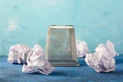 Umgekehrter Papierbehälter mit zerstreuten Papieren herum Schöner Hintergrund mit Platz für Text Ein leerer Abfalleimer zur Spitz stockbild
