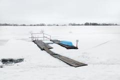 Umgekehrtes Boot auf dem Pier mit Schneefluß Stockfotos