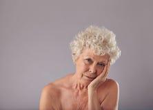 Umgekippte ältere Frau auf grauem Hintergrund Lizenzfreie Stockfotografie