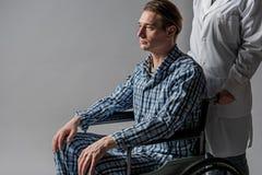 Umgekippte behinderte empfangende Sorgfalt von der Pflegekraft Lizenzfreie Stockfotos