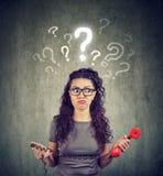 Umgekippte besorgte verwirrte Frau mit Telefon hat viele Fragen Lizenzfreies Stockbild