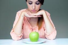 Umgekippte Brunettefrau mit grünem Apfel auf einer Platte Stockfoto