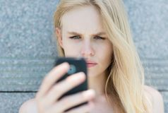 Umgekippte Frau, die ein Mobiltelefon hält stockfotos