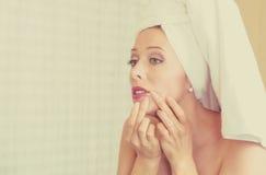 Umgekippte Frau, die in einem Spiegel frustriert schaut, um zit auf ihrem Gesicht, Pickel zu sehen lizenzfreie stockbilder