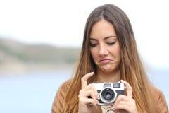 Umgekippte Frau, die ihre alte slr Fotokamera schaut Stockfotografie
