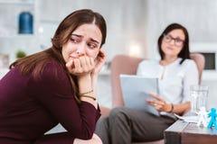Umgekippte Frau, die ihren Kopf beim Besuchen eines Psychologen dreht Lizenzfreie Stockbilder