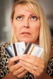 Umgekippte Frau, die an ihren vielen Kreditkarten glänzt Lizenzfreies Stockfoto