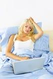 Umgekippte Frau, die im Bett mit Computer sitzt Stockbilder