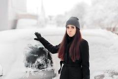Umgekippte Frau, die Schnee von einem Auto-Fenster entfernt stockfoto