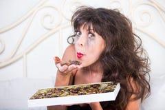 Umgekippte Frau glaubt ein wenig besseres, nachdem sie Schokoladen im Bett gegessen hat stockfoto