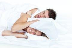 Umgekippte Frau im Bett mit ihrem schnarchenden Freund Lizenzfreie Stockfotos