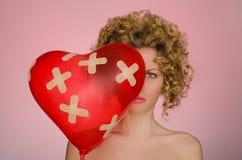 Umgekippte Frau mit Ball in Form des Herzens Lizenzfreie Stockfotografie