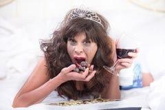 Umgekippte Frau in Tiara Drinking Wine und in vollstopfenden Schokoladen in ist Stockbild