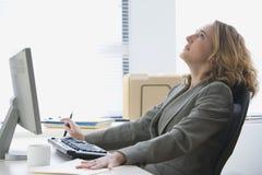 Umgekippte Geschäftsfrau, die im Büro arbeitet Lizenzfreies Stockbild