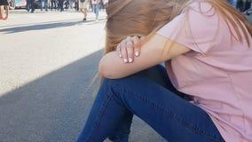 Umgekippte Jugendliche, die auf Bürgersteig, Einsamkeit, jugendlicher Übergang sitzt stock footage
