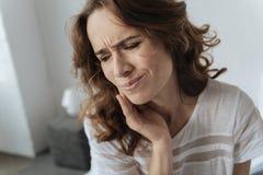 Umgekippte junge Frau, die eine Zahnschmerzen hat Lizenzfreie Stockbilder