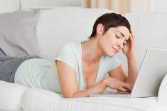 Umgekippte junge Frau, die einen Laptop verwendet Lizenzfreies Stockbild