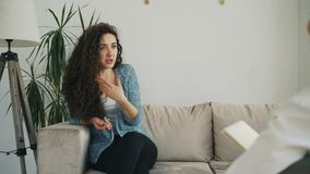 Umgekippte junge Frau, die zuhause über ihre Probleme mit professionellem weiblichem Psychoanalytiker im Psychotherapeutbüro spri