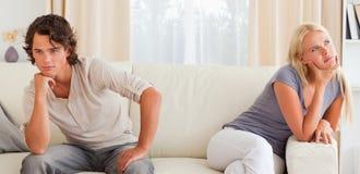 Umgekippte junge Paare, die auf einer Couch sitzen Lizenzfreie Stockbilder
