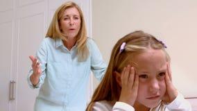 Umgekippte Mutter, die ihre Tochter schilt stock footage
