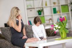 Umgekippte Mutter mit frechem Kind Lizenzfreie Stockfotografie