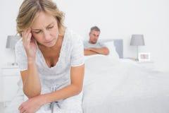 Umgekippte Paare, die an den anderen Enden des Betts nach einem Kampf sitzen Stockfoto