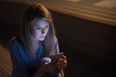 Umgekippte unglückliche Frau, die Mobiltelefon auf grauem Wandhintergrund hält Trauriges schauendes Mädchen, das auf Smartphone s Lizenzfreie Stockfotos