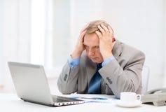Umgekippter älterer Geschäftsmann mit Laptop und Telefon lizenzfreies stockfoto