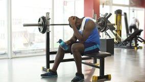 Umgekippter afro-amerikanischer Sportler, der auf Ausbildungsanlageen an der Turnhalle sitzt stock video footage