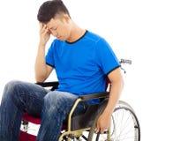 Umgekippter behinderter Mann, der auf einem Rollstuhl sitzt Lizenzfreies Stockbild