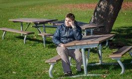 Umgekippter deprimierter Teenager, der allein im Herbstpark sitzt Stockfotografie
