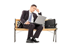 Umgekippter Geschäftsmann, der an einem Laptop arbeitet Lizenzfreie Stockbilder