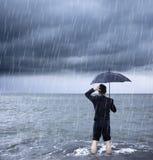 Umgekippter Geschäftsmann, der einen Regenschirm mit Wolkenbruch hält Lizenzfreie Stockfotografie