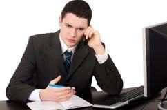 Geschäftsmann, der am Schreibtisch spricht am Telefon sitzt. Stockbild