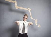 Umgekippter Geschäftsmann vor absteigendem Diagramm. Lizenzfreies Stockfoto