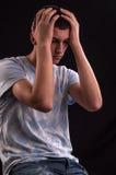 Umgekippter Jugendlicher mit dem Kopf in den Händen zuckend vom Druck, Qual O Stockfotografie