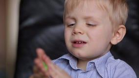 Umgekippter Junge drei Jahre, die mit buntem Teig spielen stock footage