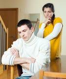 Umgekippter junger gewöhnlicher Mann gegen deprimierte Frau zu Hause Stockfotografie