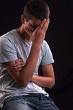 Umgekippter kaukasischer Jugendlicher mit der Hand auf Kopf Stockbild