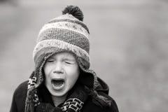 Umgekippter kleiner Junge, der heraus loud schreit Stockfoto