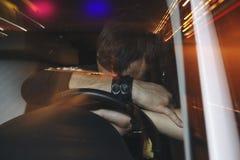 Umgekippter männlicher Fahrer ist gefangenes Fahren unter Alkoholeinfluß Mann, der sein Gesicht vom Polizeiwagenlicht bedeckt lizenzfreie stockbilder