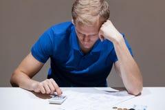 Umgekippter Mann, der Taschenrechner verwendet Lizenzfreies Stockfoto