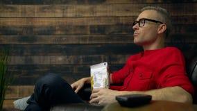 Umgekippter Mann schreit an Fernsehen beim Essen stock video footage