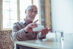 Umgekippter reifer bärtiger Mann, der geht, Vitamine zu nehmen stockfotografie