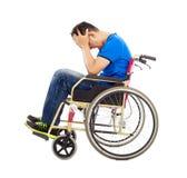 Umgekippter und behinderter Mann, der auf einem Rollstuhl sitzt Stockbilder