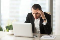 Umgekippter verwirrter Geschäftsmann, der Laptopschirm auf Arbeitsplatz betrachtet stockbild