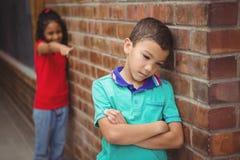 Umgekipptes Kind, das von einem anderen Kind geneckt wird Stockfotos