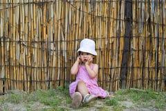 Umgekipptes kleines Mädchen, das ihren Mund mit Palmen bedeckt stockbilder